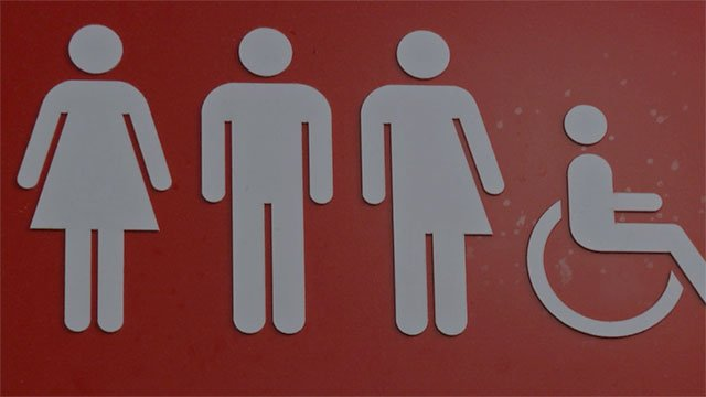 """A bathroom sign admits to """"all genders"""", in this undated photo."""