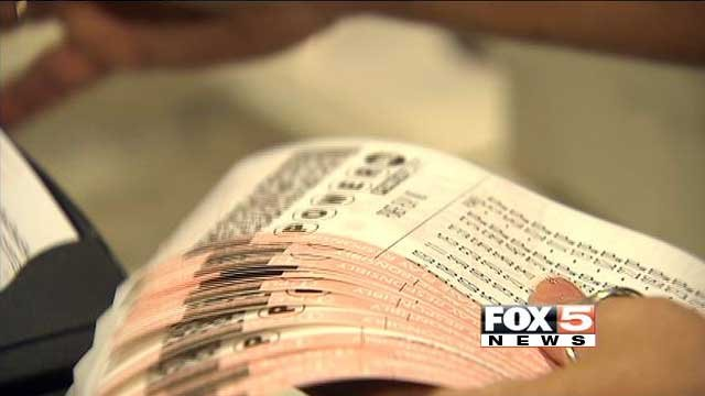 In this undated image, a lottery store patron holds a stack of Powerball tickets. (Source: File/FOX5)