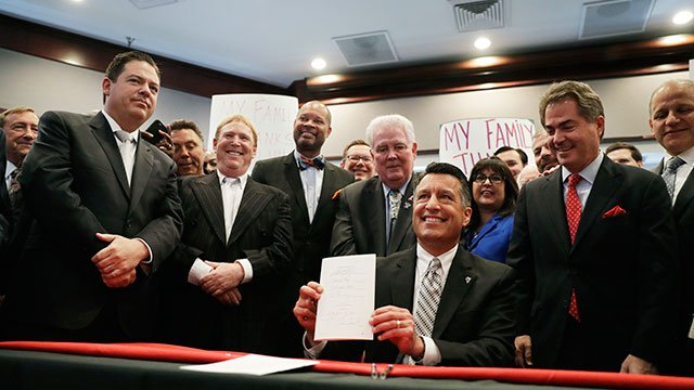 Nevada Governor Brian Sandoval holds up a bill he signed into law during a signing ceremony Monday, Oct. 17, 2016, in Las Vegas. (AP Photo/John Locher)