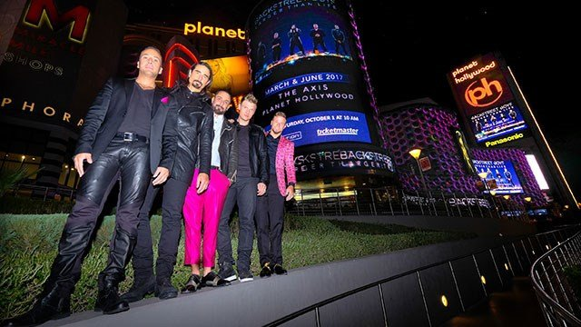 Members of the Backstreet Boys pose in front of a marquee at Planet Hollywood hotel-casino ahead of their 'Larger Than Life' residency. (Photo credit: Justin Segura)