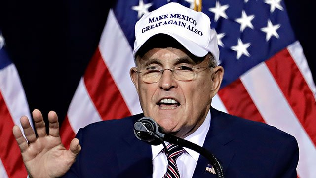 "Former mayor of New York CIty Rudy Giuliani, wears a ""Make Mexico Great Again Also"" hat prior to Republican presidential candidate Donald Trump's speech during a campaign rally at the Phoenix Convention Center, Aug. 31, 2016. (AP Photo/Matt York)"