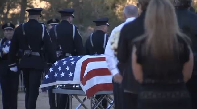 Members of an honor guard stands next to a flag-draped casket of North Las Vegas police Det. Chad Parque on Jan. 17, 2017. (FOX5)