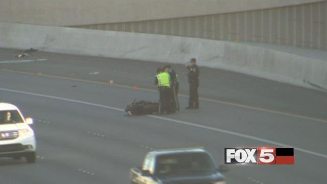 Troopers stand next to motorcycle on the ground after a rider died in a crash on U.S. 95 near Rainbow Boulevard on Jan. 24, 2017. (FOX5)