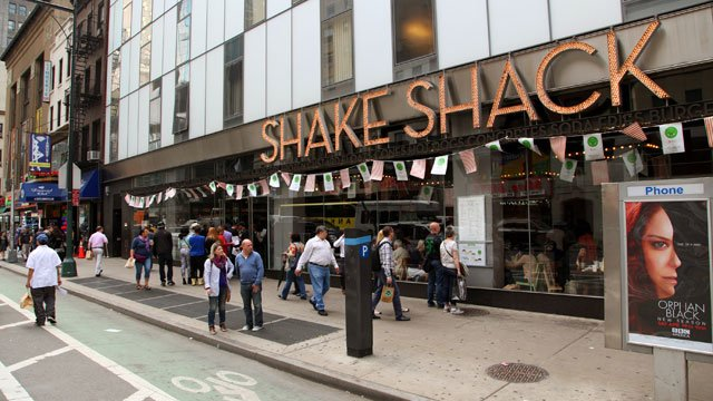 This May 21, 2014 photo shows the exterior of Shake Shack in New York's theater district. Shake Shack's upscale fast food outpost offers burgers, hot dogs, fries and shakes courtesy of restaurateur Danny Meyer. (AP Photo/Mark Kennedy)