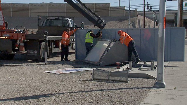 Workers try to lift a collapsed bus stop shelter after a crash near Sahara Avenue and Sandhill Road on Feb. 24, 2017. (Armando Navarro/FOX5)