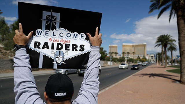 A man celebrates holding a Raiders sign, Monday, March 27, 2017, in Las Vegas. NFL team owners approved the move of the Raiders to Las Vegas in a vote at an NFL football annual meeting in Phoenix. (AP Photo/John Locher)
