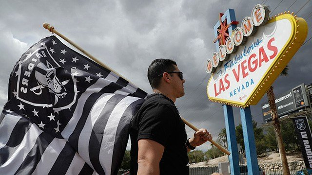 Matt Gutierrez carries a raiders flag by a sign welcoming visitors to Las Vegas on March 27, 2017. (AP Photo/John Locher)