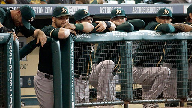 Members of the Oakland Athletics watch from the dugout during the ninth inning of a baseball game against the Houston Astros Wednesday, July 30, 2014, in Houston. The Astros won 8-1. (AP Photo/David J. Phillip)