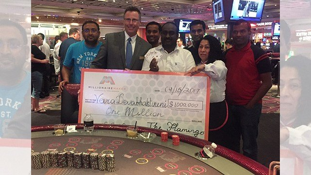 Veera Devabhaktineni holds his million-dollar winning six-card diamond royal flush along with his check for $1 million on April 15, 2017. (Source: Caesars Entertainment)