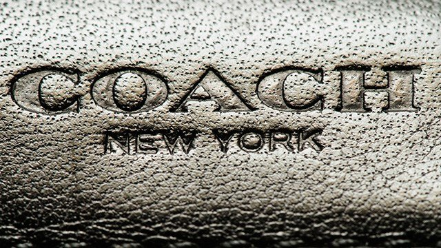 This photo shows a Coach brand logo on a leather wallet in Philadelphia, Monday, May 8, 2017. Coach will spend $2.4 billion for Kate Spade, tying together two premier brands in the luxury goods sector that have fought to snare younger shoppers. (AP Photo)
