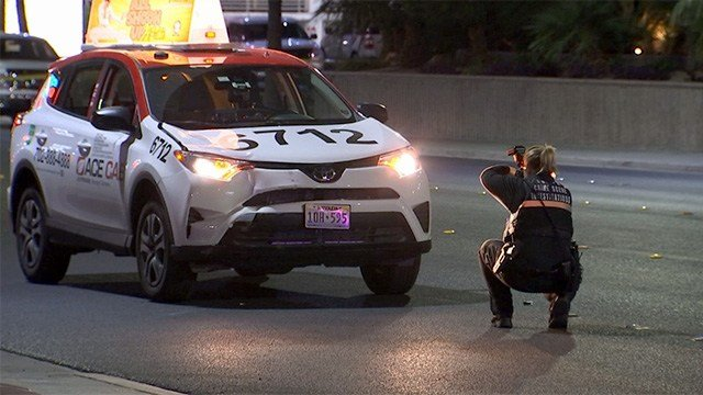 A Metro police investigator photographs a taxi cab that was involved in a deadly pedestrian crash on Convention Center Drive on May 8, 2017. (FOX5)