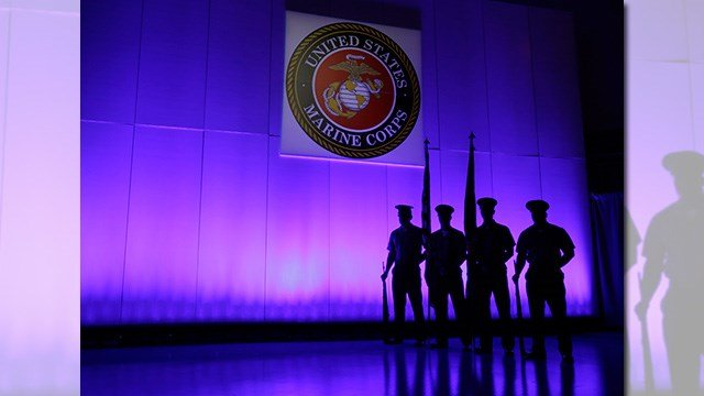 FILE- In this May 5, 2014, file photo, a U.S. Marine Corps Color Guard stands under a Marine Corps emblem in Jupiter, Fla. (AP Photo/Wilfredo Lee, File)