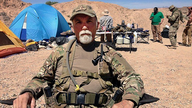 "FILE - In this April 16, 2014 file photo, Gerald ""Jerry"" DeLemus, of Rochester, N.H., sits with a group of self-described militia members camping on rancher Cliven Bundy's ranch near Bunkerville, Nev.   (AP Photo/Ken Ritter, File)"