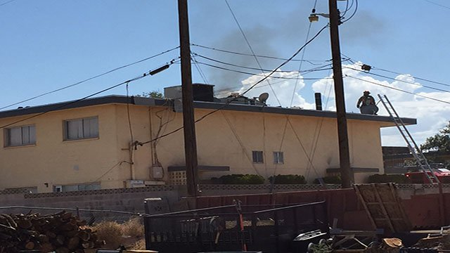 Smoke rises from the roof of an apartment building after workers accidentally started a fire while sealing shingles with a torch (LVFR).