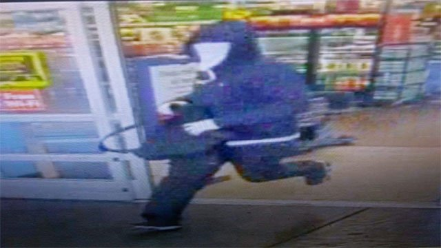 A third suspect wanted for the robbery flees the store with a duffel bag (LVMPD).