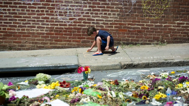 A boy draws a heart on the sidewalk in Charlottesville, Va., on Aug 18, 2017, near the site where Heather Heyer was killed during a rally. (AP Photo/Cliff Owen)