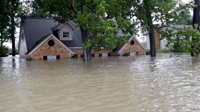 In this Aug. 28 photo, a home is surrounded by floodwaters from Tropical Storm Harvey in Spring, Texas. (David J. Phillip/AP)