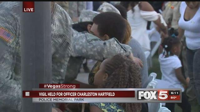 Army soldiers embrace Officer Hartfield's children as the vigil begins (FOX5).