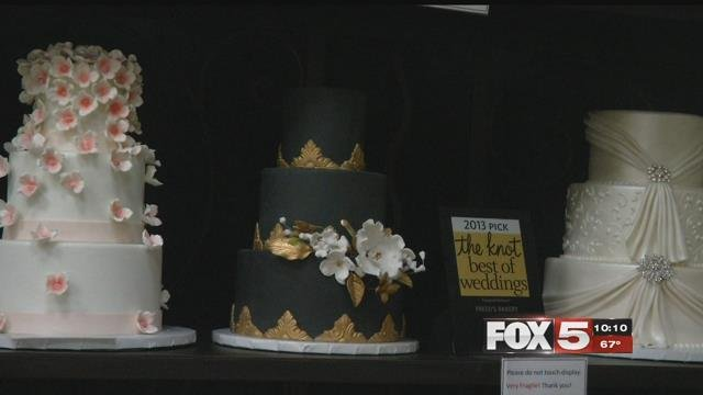 A row of elaborate wedding cakes lines a shelf at Freed's Bakery (FOX5).