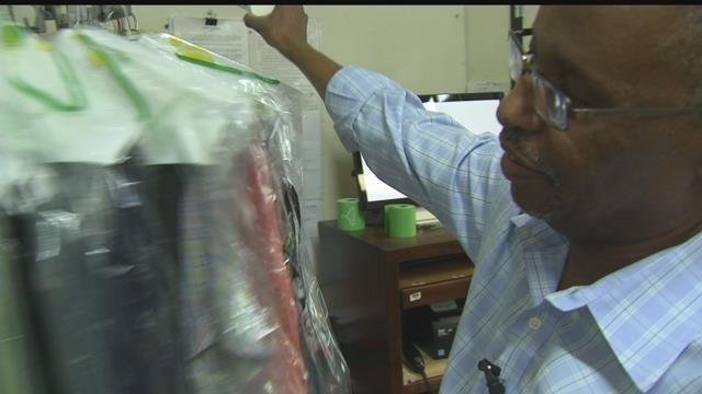 Mahamed Youssef browses through a row of dry cleaned uniforms (FOX5).