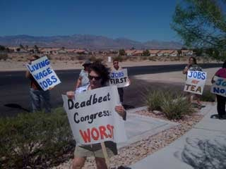 Protesters hold signs outside a forum on jobs held by Rep. Joe Heck. (FOX5)