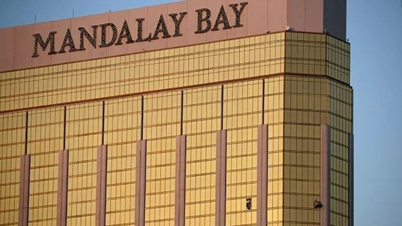 Drapes billow out of broken windows at the Mandalay Bay resort and casino Monday, Oct. 2, 2017, on the Las Vegas Strip following a deadly shooting at a music festival in Las Vegas. (AP Photo/John Locher)