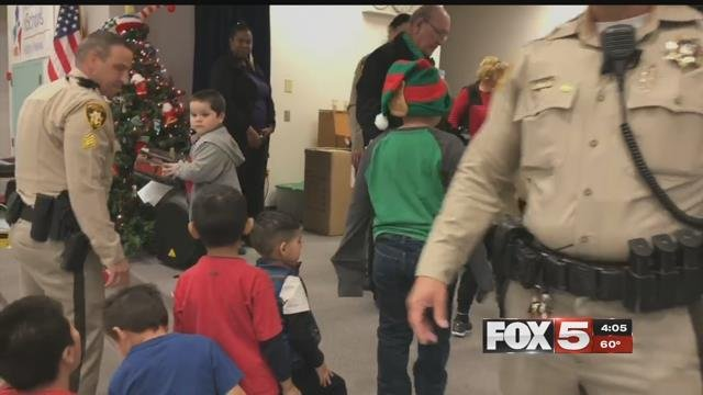 Metro officers and Bob Ellis hand out donations to students (FOX5).