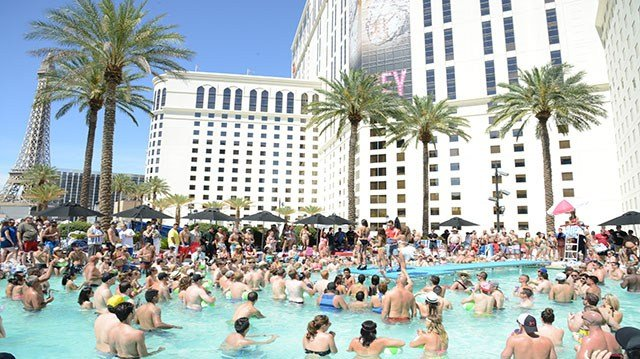 Las Vegas revelers swim in a resort pool (Caesars Entertainment).