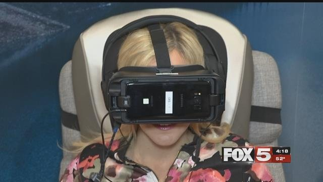FOX5's Cyndi Lundeberg tries on a virtual reality headset at CES 2018 (FOX5).