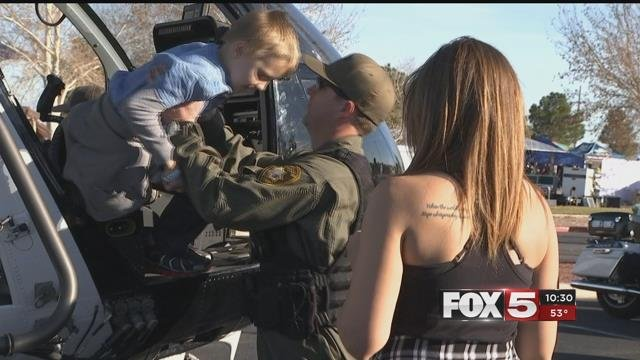 An officer lifts a child up into a police vehicle (FOX5).