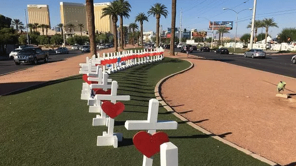 A row of 58 crosses dedicated to the victims of the mass shooting stand behind the Welcome to Fabulous Las Vegas sign (FOX5).