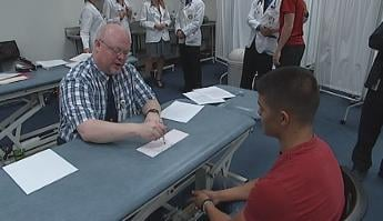 A physician reviews EKG results with a student