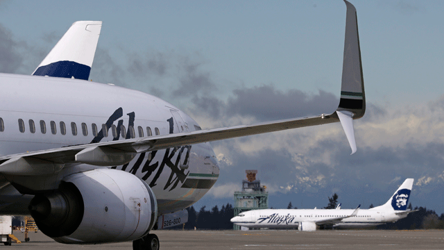 Alaska Airlines planes wait for takeoff, Monday, April 4, 2016, at Seattle-Tacoma International Airport in Seattle. (AP Photo/Ted S. Warren)
