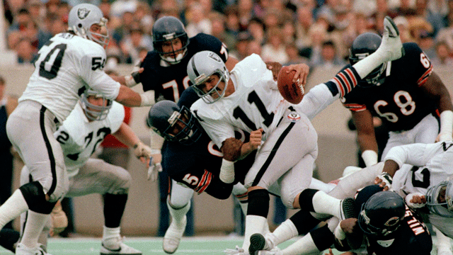 In this Nov. 5, 1984, file photo, Chicago Bears defensive end Richard Dent (95) brings down Los Angeles Raiders quarterback David Humm (11) during the first half of an NFL football game in Chicago. (AP Photo/Fred Jewell, File)