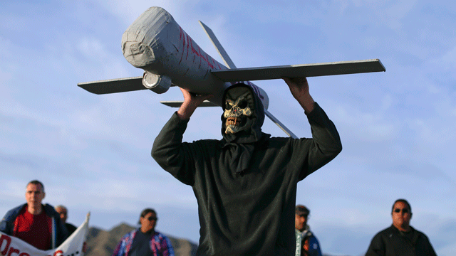 John Amidon holds up a model of an Air Force drone while protesting outside Creech Air Force Base, Wednesday, March 27, 2013, in Indian Springs, Nev. (AP Photo/Julie Jacobson)