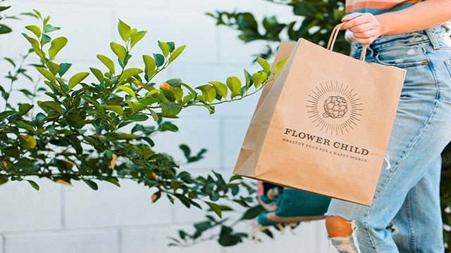 A customer holds a to-go bag from healthy fast casual eatery Flower Child (Flower Child).