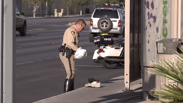 An officer collects shoes from the roadway after a crash involving a pedestrian on April 9, 2018. (Luis Marquez/FOX5)