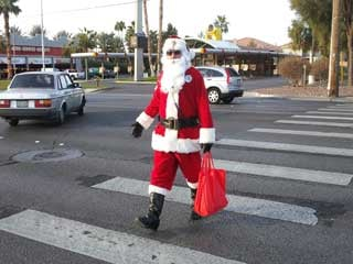 Officer in a Santa suit crossing the street