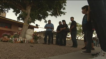 Mourners gathered in front of the Robin Street home Friday night