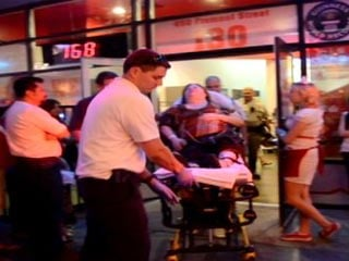 Emergency medical workers wheel a woman out of the Heart Attack Grill Saturday after suffering a medical episode there. (FOX5)