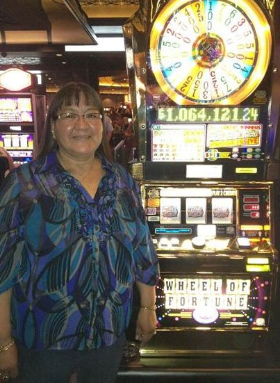 Linda Fleury stands next to the slot machine that hit the jackpot for