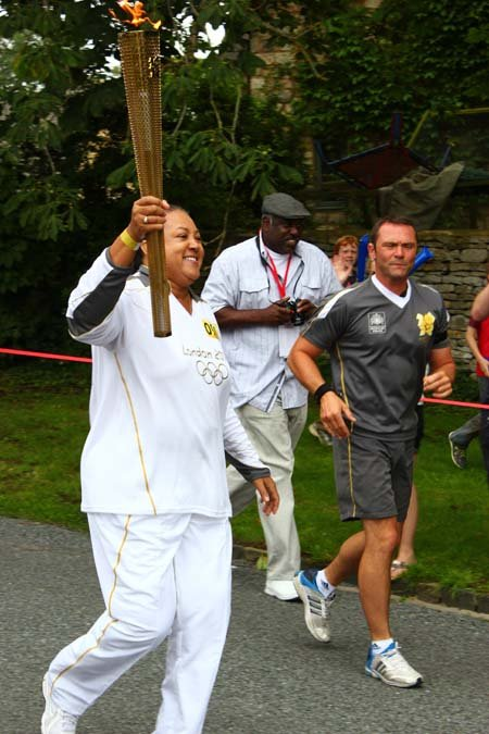 Debra Toney runs with the Olympic torch in Oxford.