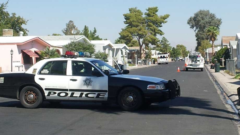 A police car blocks Death Valley Drive while crews put out a mobile home fire. (Peter Dawson/FOX5)