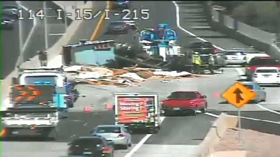An overturned semi-truck spilled what appeared to be wooden planks on the I-15 access road. (FASTCAM)