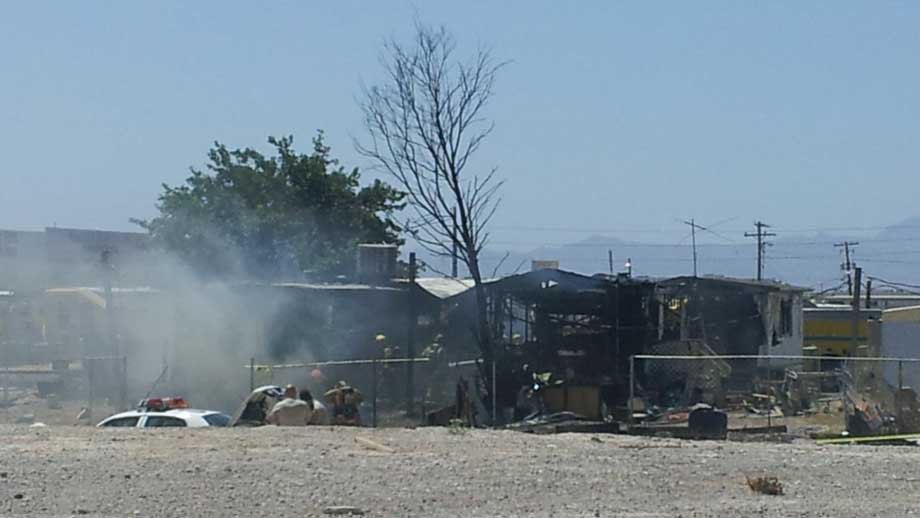 Firefighters mill through charred remains of two mobile homes Friday. (Joe Lybarger/FOX5)