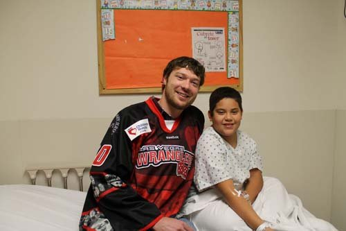 Wranglers goaltender Joe Fallon visits with a patient. (Danny Romero)