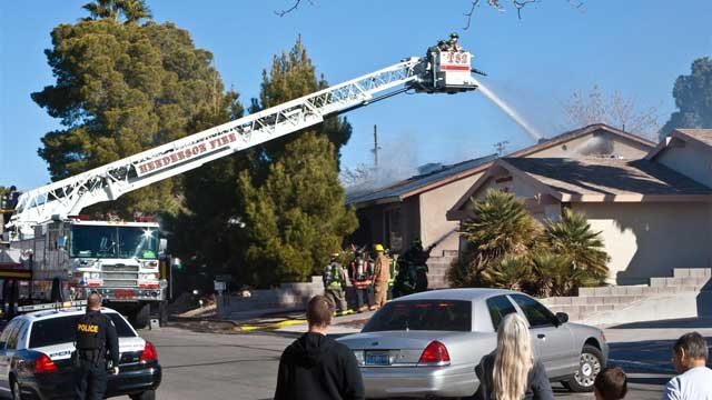 A Henderson fire crew extinguishes a blaze at a home where a reported homicide took place. (Courtesy: John Calvert)