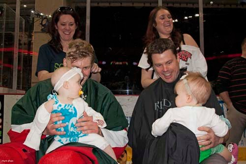 Wranglers forward Robbie Smith and Head Coach Ryan Mougenel get their heads shaved as their daughters look on. (Photo by Angela Cripps)