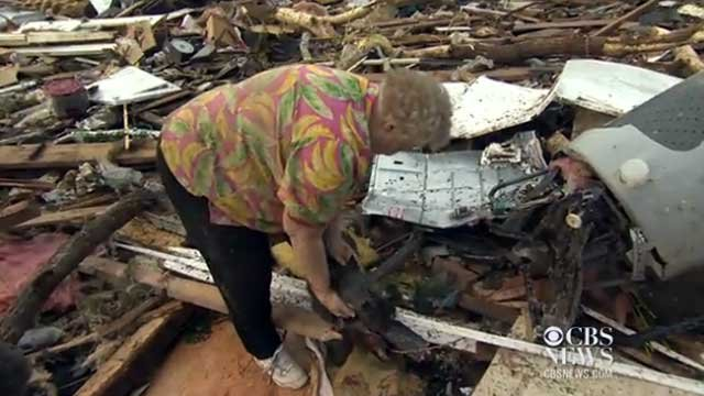 Barbara Garcia lifts her dog from the rubble of a tornado. (Source: CBS News/cbsnews.com)