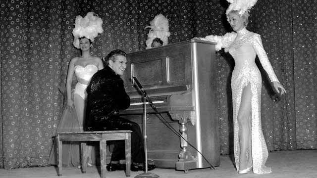 "Liberace's ""Piano Roll Blues"" rolled out the carpet at the premier of Las Vegas' new sky-scraper Hotel Riviera on April 21, 1955. His attire was designed by Dior and supporting him are the hotel chorines. (AP Photo)"